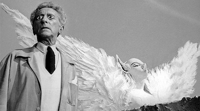 Cocteau, wearing false eyes and standing next to a statue