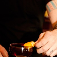 Bradley Bolt of Bar DeVille makes the Blind of Eye Express the oils from the orange peel onto the surface of the drink. Andrea Bauer