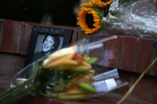 Flowers and pictures that are part of a growing memorial sit on the steps in front of the home where Robin Williams filmed the movie Mrs. Doubtfire.
