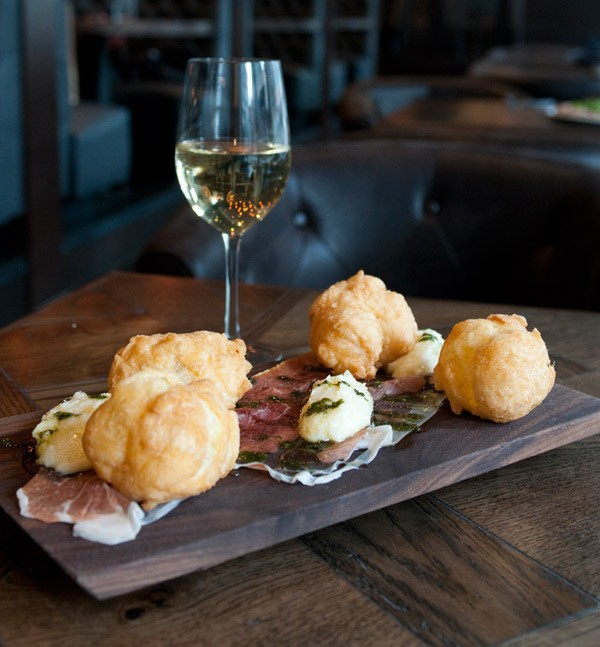 Fried dough pufflets with truffle-honeyed sheets of prosciutto and a creamy lump of stracchino cheese