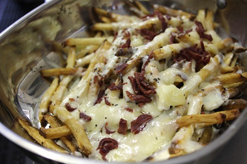 Fries with bechamel sauce, cheese and duck bacon