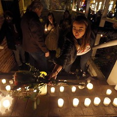 Jenifer Trotter, sister-in-law to Charlie Trotter, places a bouquet of flowers with candles on the steps of the latter's former restaurant during a candlelight tribute to the chef last night.