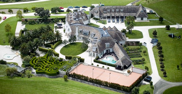 Left: Megaupload founder Kim Dotcom in happier days. Above: The mansion Dotcom was renting in Coatesville, New Zealand, at the time of his arrest.