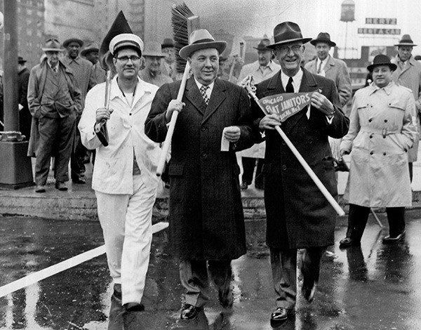 Mayor Richard J. Daley marches with members of the janitors' union in 1957. But over the last two decades, mayors Richard M. Daley and Rahm Emanuel have privatized or cut hundreds of custodial jobs.