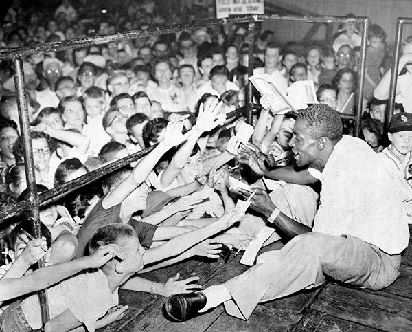 Minnie Minoso, who in 1951 became the first black White Sox player, signs autographs at the Chicago Free Fair in the Back of the Yards neighborhood in 1957. - SUN-TIMES PRINT COLLECTION