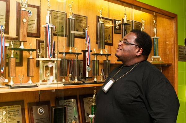 [photograph of Kelvyn Cockrell at the trophy case]