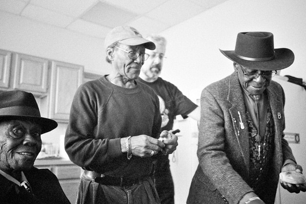 "Pinetop Perkins, Willie ""Big Eyes"" Smith, and Bob Stroger take a bagel break in the studio's kitchen. The author is in the background. - ""Pine was like a brother and a father to me. He is the reason why I play the blues,"" Stroger said. - JESSE LIROLA"
