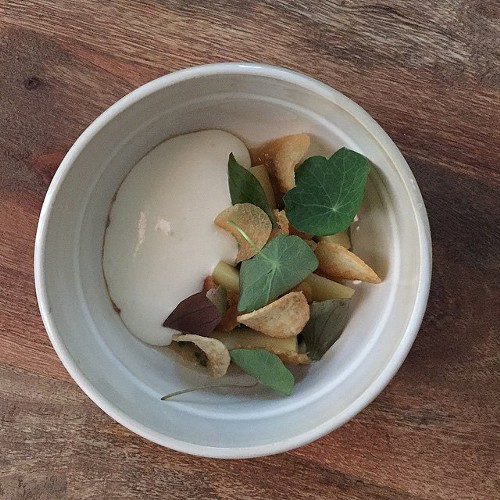 Potato espuma with confit potatoes, miners lettuce, nasturtium, and chicken skins, from Aaron Martinezs popup at Elizabeth