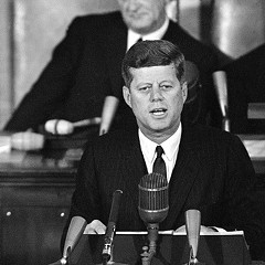 President John F. Kennedy, speaking in the House chamber in January 1963, with Vice-President Lyndon Johnson behind him.  Kennedy put poverty on the presidential agenda, but it was Johnson who set the War on Poverty in motion.