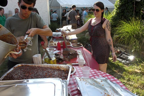 Rae Hill (with knife) presides over the Burnin BBQ spread.