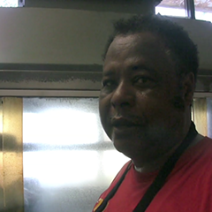 Robert Adams Sr. in front of his glass pit at Honey 1 BBQ