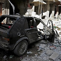Syrian citizens gather at the scene of a car bomb explosion in the residential al-Tadhamon neighborhood in Damascus.