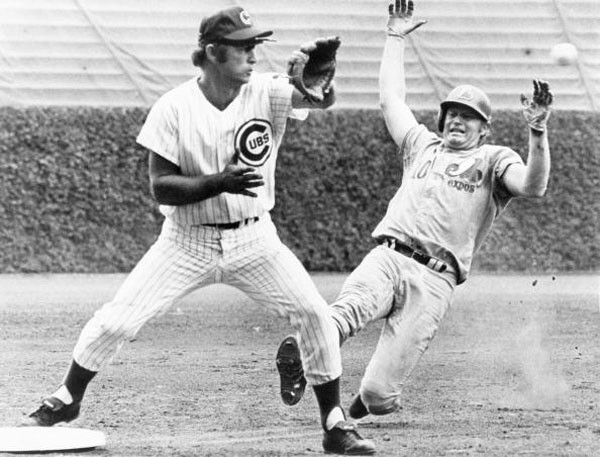 Third baseman Ron Santo #10 of the Chicago Cubs waits for the ball as Rusty Staub #10 of the Montreal Expos slides in during a game at Wrigley Field in Chicago, Illinois in 1969.