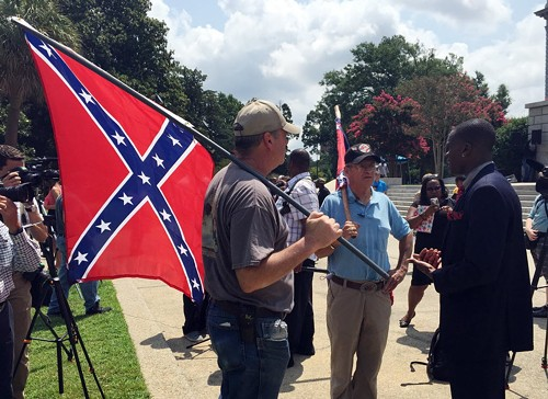 Three men—two from South Carolina, one from Georgia—discussed the Confederate flag outside the South Carolina Statehouse earlier today. - MEG KINNARD/AP PHOTOS