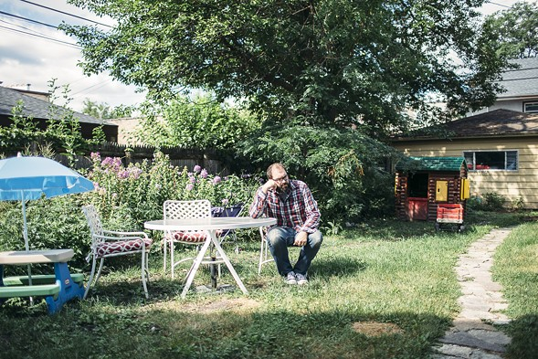 Owen Ashworth in his west-suburban backyard. Not pictured: his daughters, who have a much easier time fitting into that toy log cabin. - JEFFREY MARINI