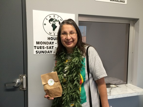 On Tuesday, Michelle DiGiacomo donned a marijuana lei as she made her first legal medical pot purchase at EarthMed in Addison, one of eight dispensaries that opened for business this week in Illinois. - COURTESY MICHELLE DIGIACOMO