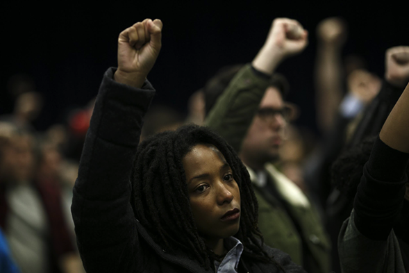 Attendees raise their fists in protest during the November Police Board meeting Thursday. - JONATHAN GIBBY