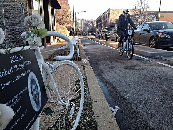 A woman rides down the Clybourn protected bike lane, past the 'ghost bike' memorial to Bobby Cann. - JOHN GREENFIELD