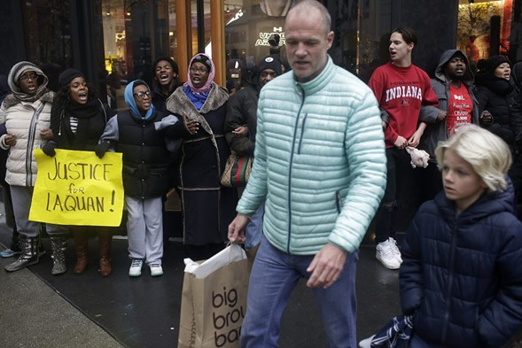 Shoppers walk past demonstrators blocking the entrance to the Michigan Avenue Under Armour store on Black Friday. - JOSHUA LOTT/GETTY IMAGES
