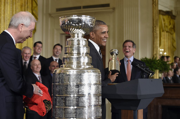 President Obama, flanked by Blackhawks president John McDonough, left, and chairman Rocky Wirtz, holds up a small version of the Stanley Cup during a ceremony at the White House Thursday. - AP/SUSAN WALSH