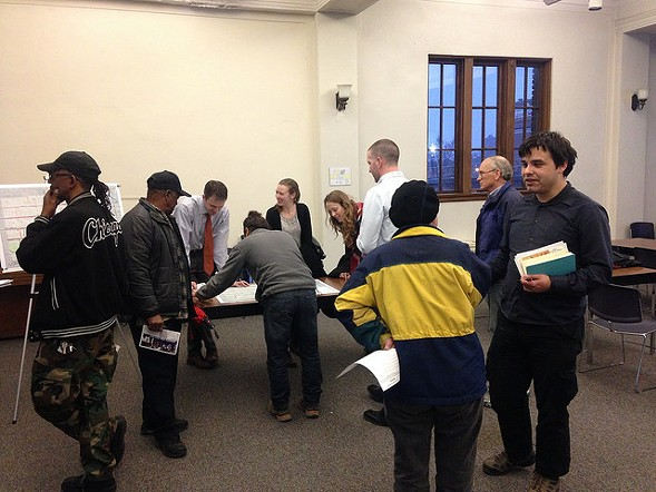 Meeting attendees, including Mark Yalverton, left, and Jerome Montgomery, second from left, discuss bike routes with CDOT staff and consultants at the Legler Library last Wednesday. - CHICAGO DEPARTMENT OF TRANSPORTATION