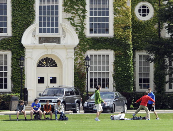 Students play catch with a football in front of Lake Forest High School in Lake Forest, one of the area's most affluent suburbs. - ROB DICKER/SUN-TIMES MEDIA