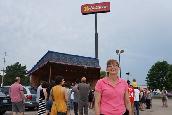 Denice Hubbs, manager of Rock 'n' Roll Hardee's, in front of the Dumb Fest crowd and the restaurant's outdoor stage - SEAN NEUMANN