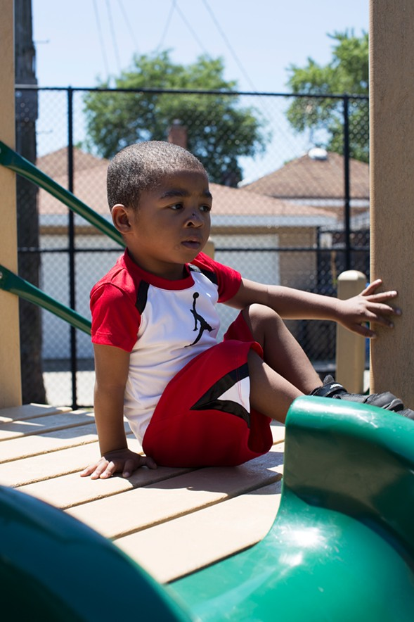 Two-and-a-half-year-old Noah in a playlot behind the Metropolitan Family Services office. Noah and his family receive home visits from the agency. - SUNSHINE TUCKER