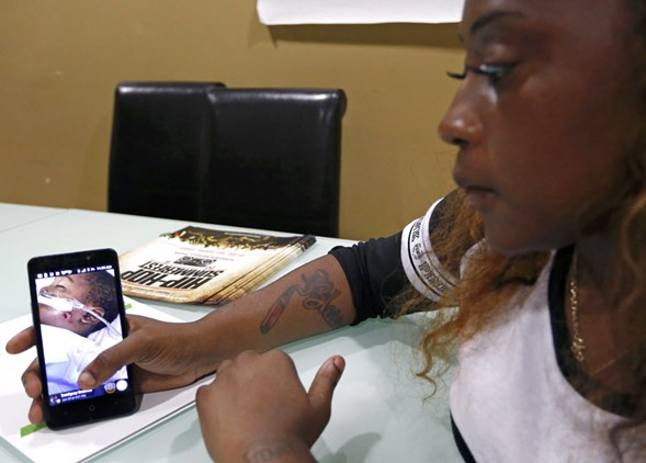 D'Antignay Brashear shows a photo of her four-year-old son, Kavan Collins, after he was shot on June 28 in Chicago. - AP PHOTO/TAE-GYUN KIM