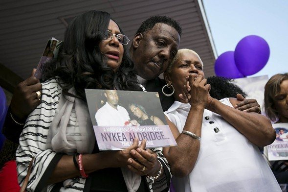 Family members and supporters hug Diann Aldridge during a vigil for her daughter Nykea Aldridge Sunday. - ASHLEE REZIN/CHICAGO SUN-TIMES VIA AP