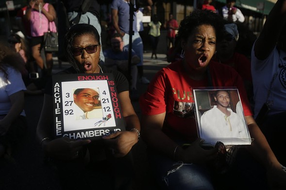 Antoinette Marshabanks, left, holds a photos of her son Archie Lee Chambers Jr. and Sharon Miles holds a picture of her son Korey Parker during a sit-in as they protest the recent rise in homicides across the city. - PHOTO BY JOSHUA LOTT/GETTY IMAGES