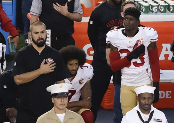 San Francisco 49ers quarterback Colin Kaepernick, middle, kneels during the national anthem at a preseason game Thursday. - AP PHOTO/CHRIS CARLSON