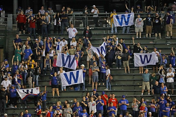 Fans in the bleachers hold W flags after the Cubs beat the Cincinnati Reds Wednesday. - JONATHAN DANIEL/GETTY IMAGES