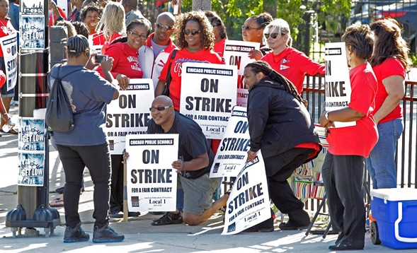 Chicago Public Schools teachers take a group picture as they walk a picket line in 2012. - AP PHOTO/M. SPENCER GREEN