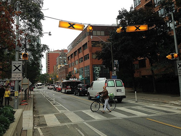 Button-activated beacons make it safer to cross the street mid-block. - JOHN GREENFIELD
