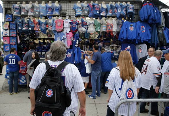 Fans look at Cubs merch outside Wrigley Field before game two of the NLCS. - AP PHOTO/CHARLES REX ARBOGAST