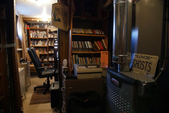 Ghost knickknacks, books on paranormal phenomena, and other research materials fill the basement. - KERRI PANG