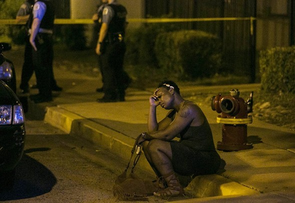 A woman sits on the curb as police investigate an August scene where gunfire at a birthday party left a man dead and a woman injured. - ASHLEE REZIN/SUN-TIMES VIA AP