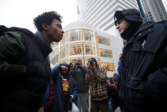 Activist Lamon Reccord, left, stares down a police officer during a black Friday protest along the Michigan Avenue in November 2015. - JOSHUA LOTT/GETTY IMAGES