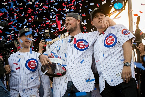 Jon Lester, flanked by Chris Coghlan and Anthony Rizzo, holds the Commissioner's Trophy during the Chicago Cubs' World Series rally in Grant Park. - ASHLEE REZIN/SUN-TIMES