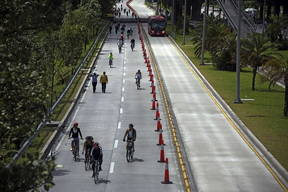 Riders and pedestrians enjoy Bogotá's weekly Ciclovía on streets temporarily closed to motor vehicles. - EITAN ABRAMOVICH/GETTY IMAGES