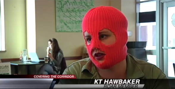 The author, sporting a ski mask, during a post-protest interview with Iowa City's CBS affiliate KGAN.