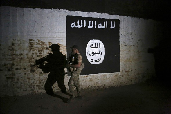 An Iraqi soldier in the city of Mosul inspects a train tunnel bearing the flag of ISIS. - AP PHOTO/KHALID MOHAMMED, FILE