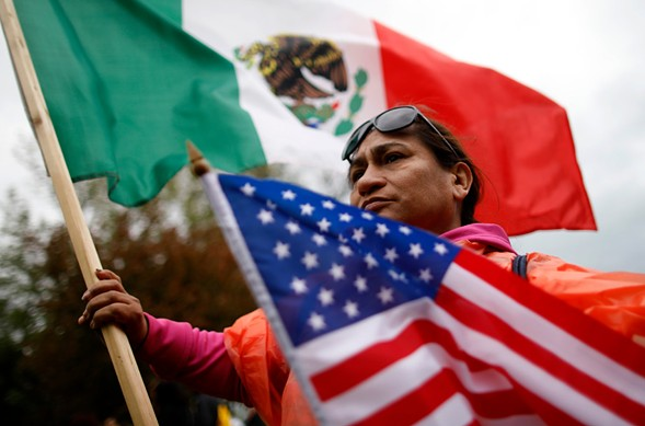 A protester holds U.S. and Mexico flags during May Day demonstrations in Chicago. - JIM YOUNG/AFP/GETTY IMAGES