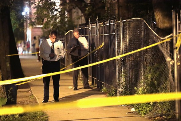 Police search for evidence after a man was shot over Memorial Day Weekend. - PHOTO BY SCOTT OLSON/GETTY IMAGES