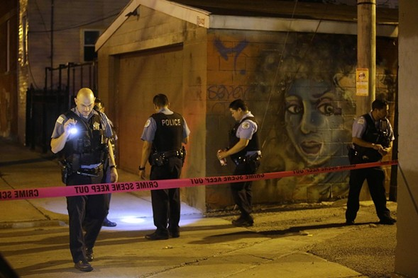 Police officers investigate the crime scene where a man was shot in the alley in the Little Village neighborhood in Chicago on July 2. - AFP PHOTO / JOSHUA LOTT