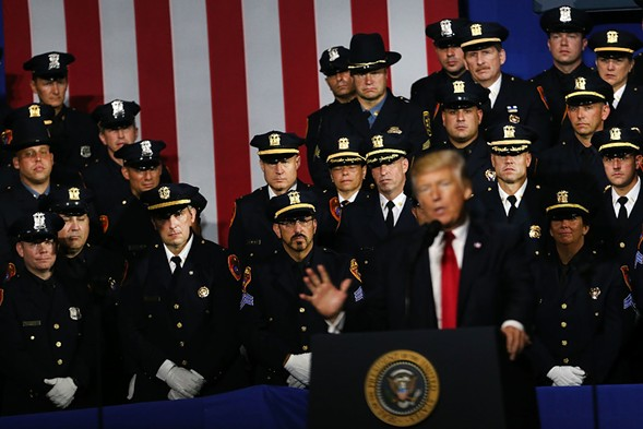 Police officers look on as President Donald Trump speaks in New York in July. - PHOTO BY SPENCER PLATT/GETTY IMAGES