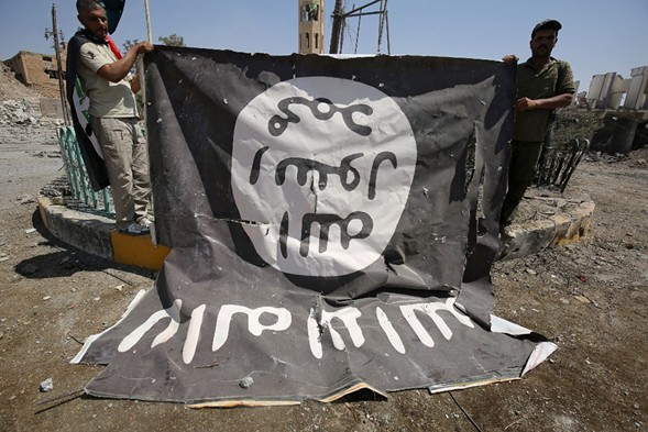 Fighters pose for a photograph with a flag of the Islamic State