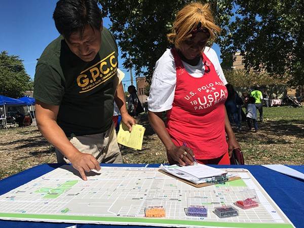Garfield Park residents contributing to the Vision Zero West Side map of community concerns at the Garfield Park Farmers Market in September. - CDOT