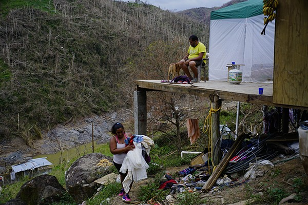 """Puerto Rican residents Yadira Sortre and William Fontan Quintero with what remains of their house after Hurricane Maria. """"We lost everything,"""" Quintero says. They have three children, one of whom lives in Chicago. - RAMON ESPINOSA"""